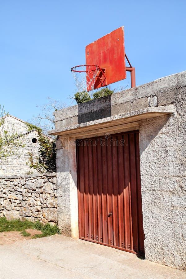 Tablero rojo del baloncesto en el edificio imagen de archivo