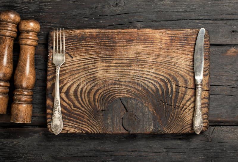 Tablero vacío del vintage con la bifurcación y cuchillo en la tabla de madera imágenes de archivo libres de regalías