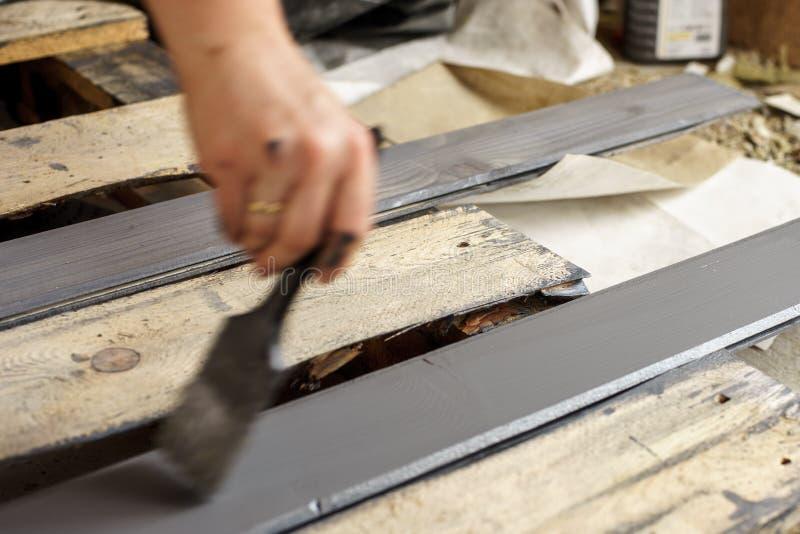 Tableros de pintura con un cepillo sostenido a disposición Gris, pintura de madera de antracita imagen de archivo