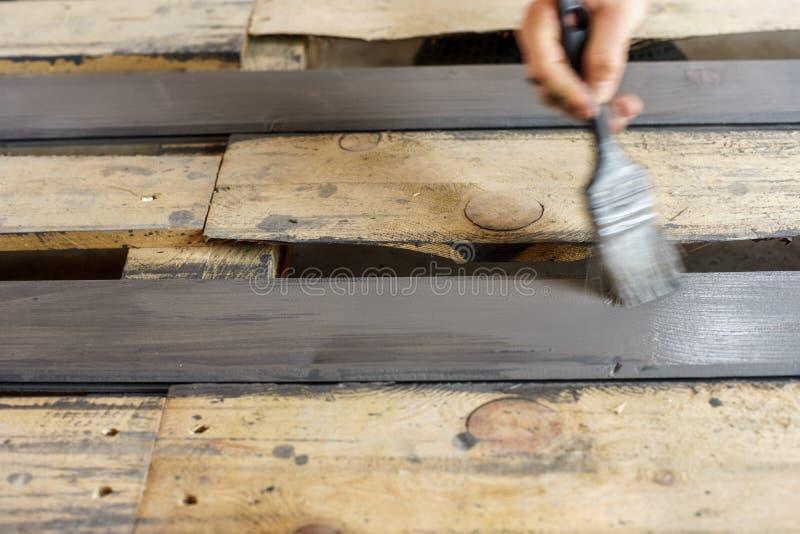 Tableros de pintura con un cepillo sostenido a disposición Gris, pintura de madera de antracita fotos de archivo libres de regalías