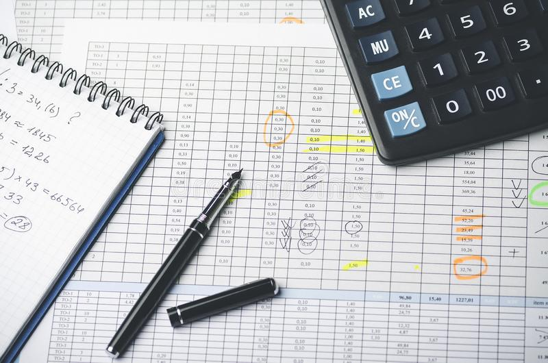 Tables with accounting figures, pen, paper notebook and calculator. Top view stock images
