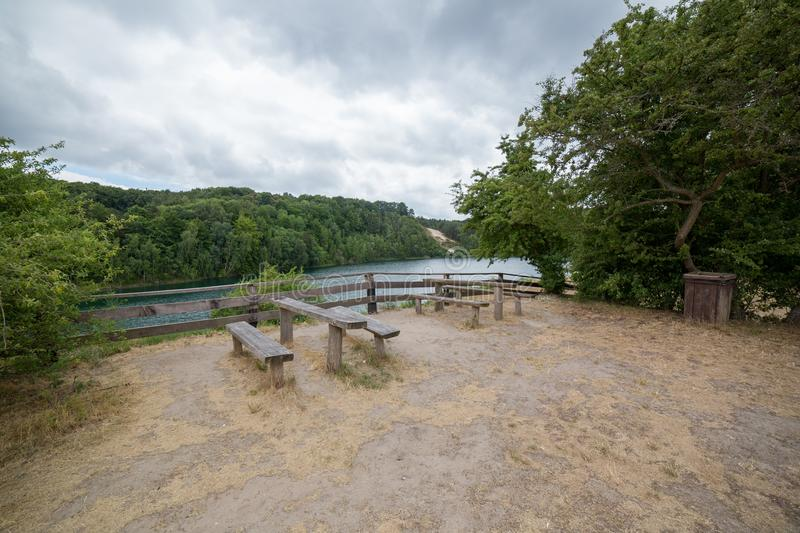 Tables with benches on picnic area near lake in park royalty free stock images