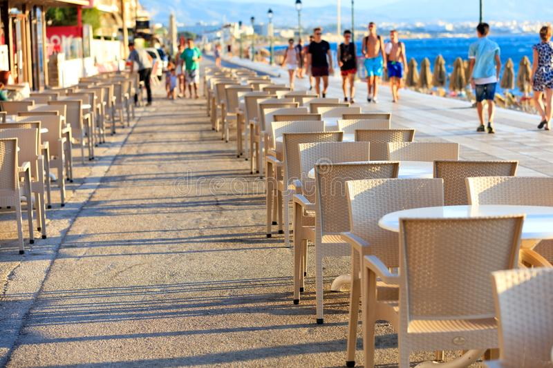 The tables and chairs of the beach cafe are located along the promenade among people walking near the blue sea in blur. Tables and chairs of the beach cafe are royalty free stock photos