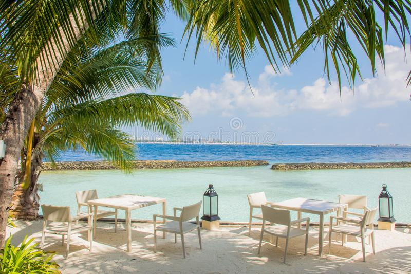 Tables and chairs in the luxury outdoor restaurant at the tropical island royalty free stock image