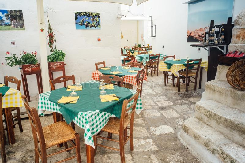 Tables and chairs of an outdoor restaurant on the streets of the historic center in ostuni, Italy stock image