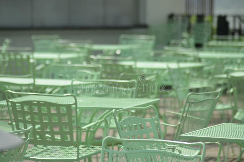 Empty green table and chair. Tables and chairs sit empty in the outdoor restaurant in lower Manhattan in nyc before the lunch and diner service begins stock photo