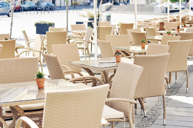 Tables and chairs on a terrace. Row of tables on a terrace in the center of the city royalty free stock photos