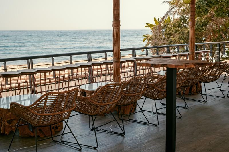 Tables and chairs on the terrace by the sea royalty free stock photography