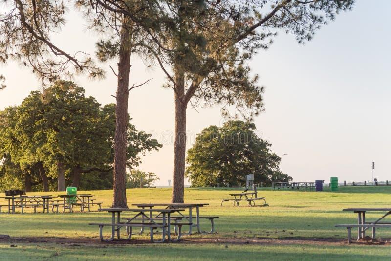 Tables de pique-nique vides en m?tal au beau parc avec beaucoup d'arbres au coucher du soleil en Am?rique images stock
