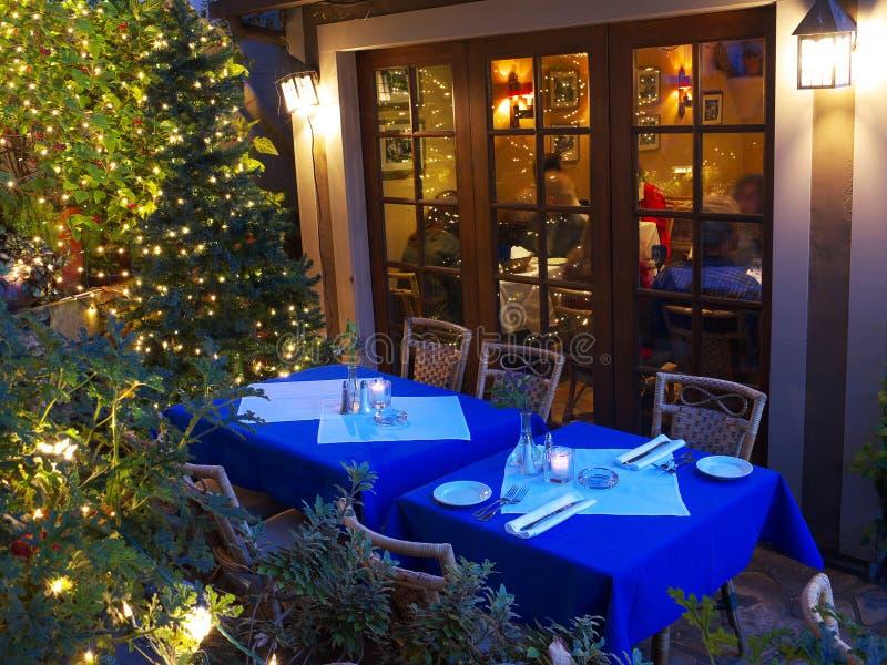 Tables de restaurant dans la lumière de Noël images stock