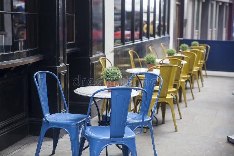 Tables multicolores dans un café de rue sur le Carnaby Street photographie stock
