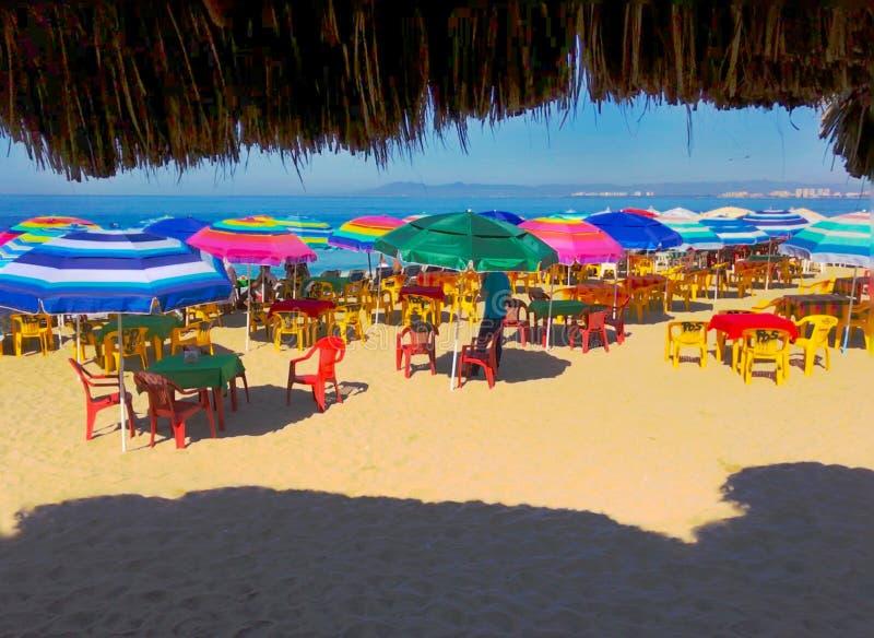 Tables Puerto Vallarta sur la plage avec parasols colorés images libres de droits