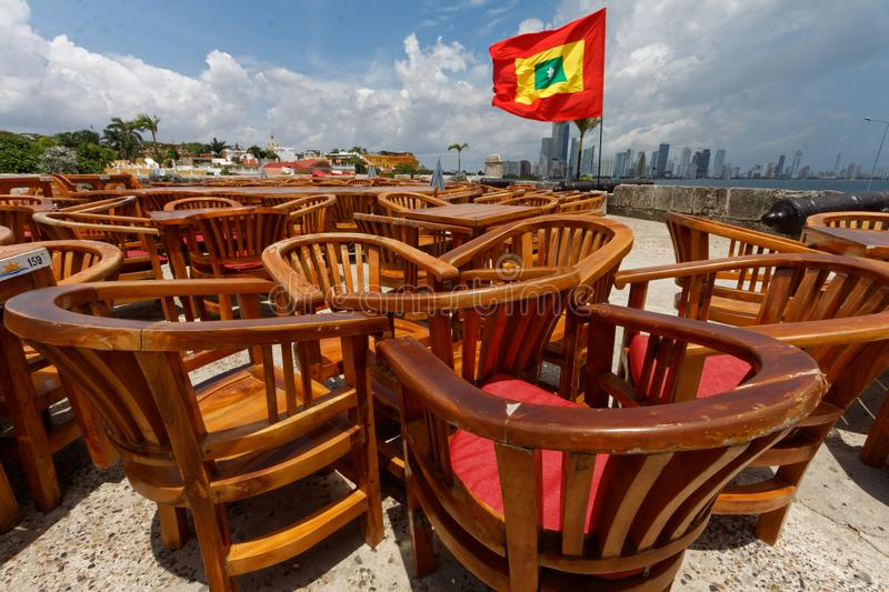 Tables of a ramparts restaurant 3. Tables and chairs of a ramparts restaurant with a flag. Chairs and tables made of wood. On a clear sunny summer day. Blue sky stock images