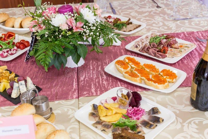 Tables servies au banquet Boissons, casse-croûte, délicatesses et fleurs dans le restaurant Un gala ou un mariage photographie stock libre de droits