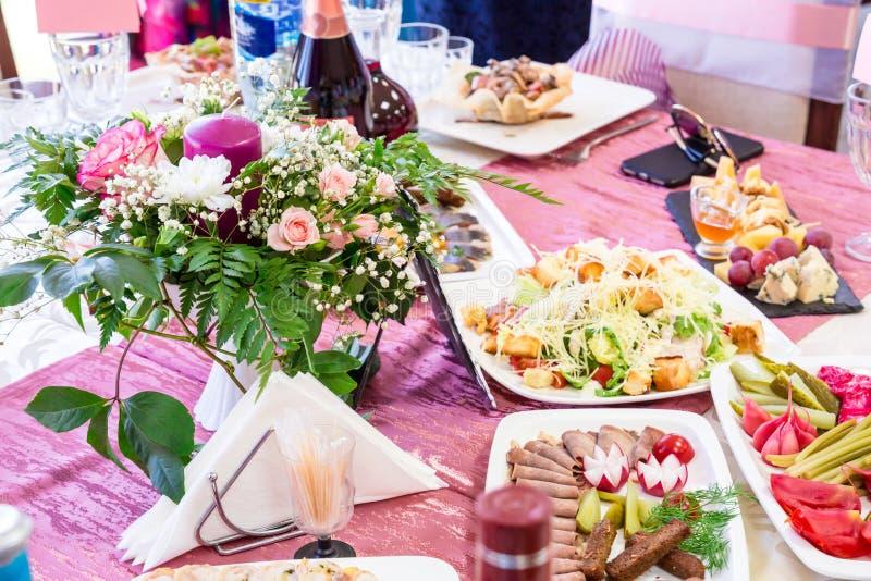 Tables servies au banquet Boissons, casse-croûte, délicatesses et fleurs dans le restaurant Un gala ou un mariage photographie stock