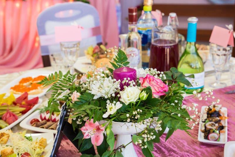 Tables servies au banquet Boissons, casse-croûte, délicatesses et fleurs dans le restaurant Un gala ou un mariage photos libres de droits