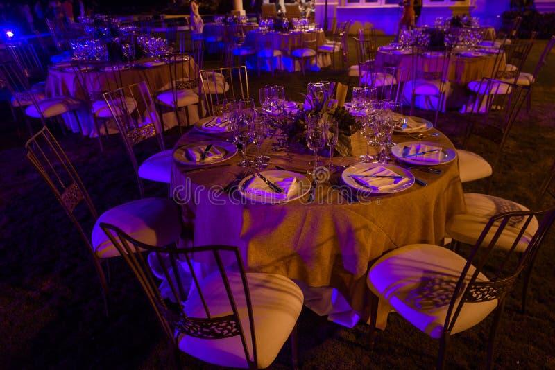Tables servies au banquet dans des tons pourpres Photo de nuit images stock
