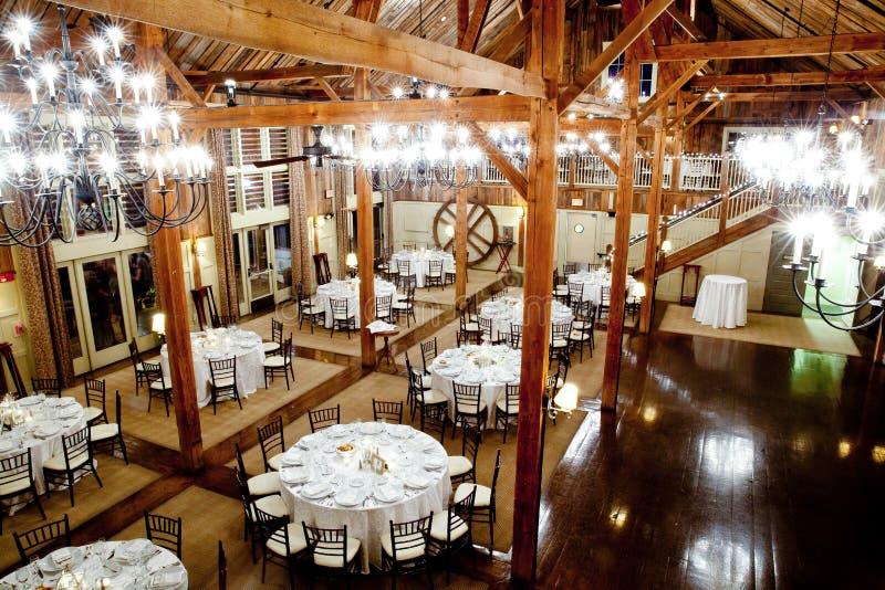 Tables set inside a big dark barn during a wedding reception. Wedding tables set inside a large dark barn during a wedding reception royalty free stock photos