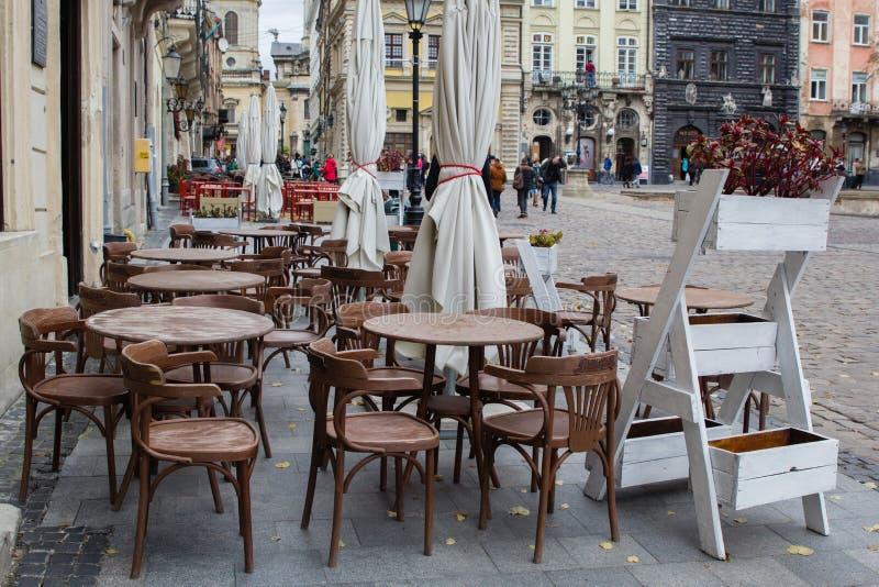 Tables vides de café extérieur au centre de la ville de Lviv photo stock