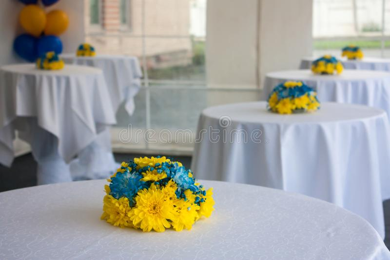 Tables with white tablecloths decorated with flowers stock image