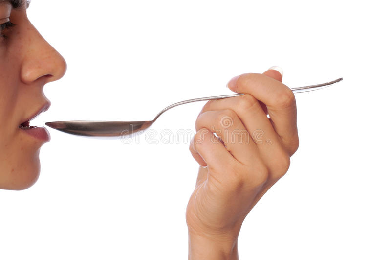 Tablespoon. Woman holding tablespoon in the hand for feeding a sick person royalty free stock photo