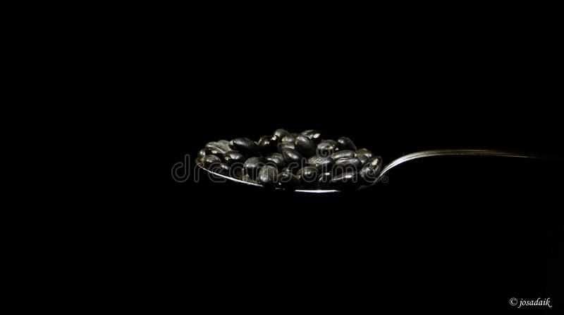 Tablespoon of beans. A tablespoon of beans in the front a black background. Feijoada, beans, tablespoon, meals, food royalty free stock image