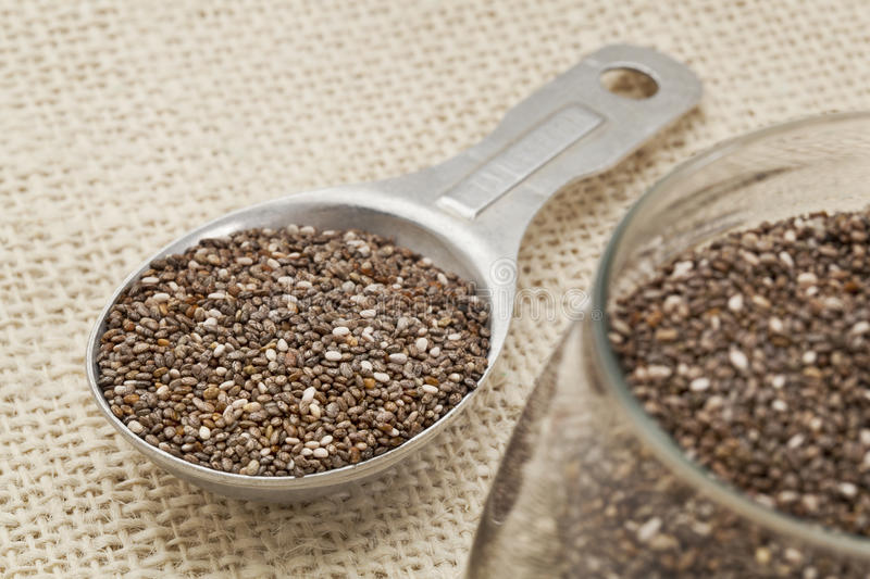 Tablespoon of chia seeds. Chia seeds in glass jar and on measuring aluminum tablespoon against burlap background, focus on the spoon stock images