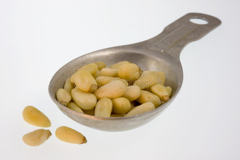 Tablespoon of pine nuts. On white stock photos
