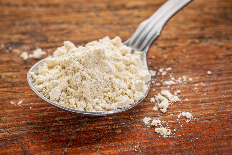 Tablespoon of quinoa flour. Tablespoon of gluten free quinoa flour against rustic wood royalty free stock image