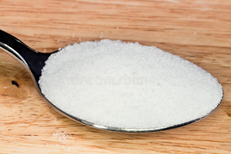 Tablespoon salt. Tablespoon of finely ground sea salt close up royalty free stock photography