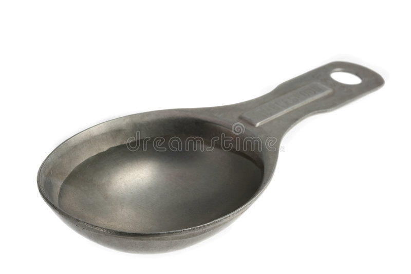 Tablespoon of water. Plain water on old, aluminum, measuring tablespoon isolated on white stock photo