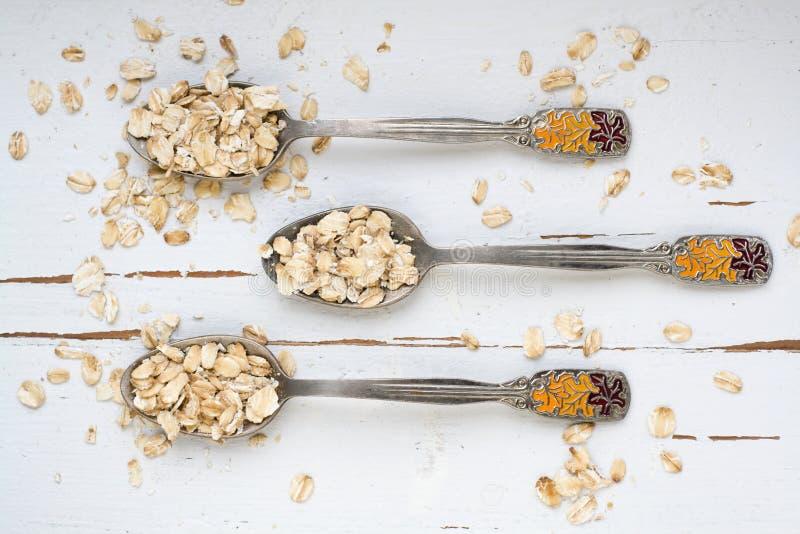 3 tablespoons овсяной каши лежа на белой деревянной предпосылке стоковые фотографии rf