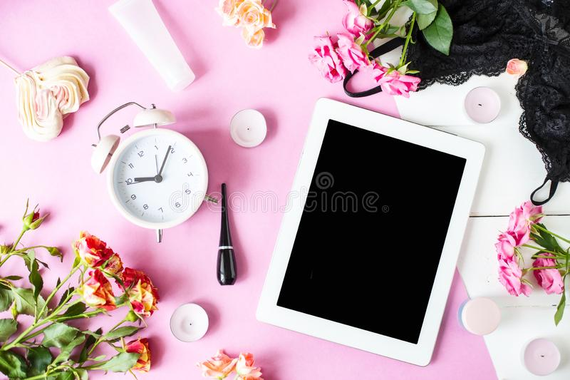 Tablet, alarm clock, underwear, roses, candles, cosmetics on the table. Women`s things Fashion womens desk stock photography