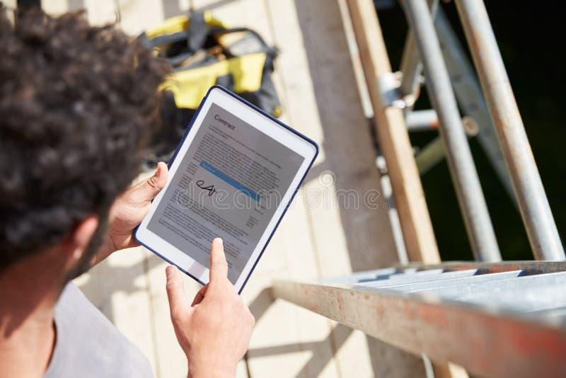 Tablet Bauarbeiter-Signing Contract Ons Digital lizenzfreies stockfoto