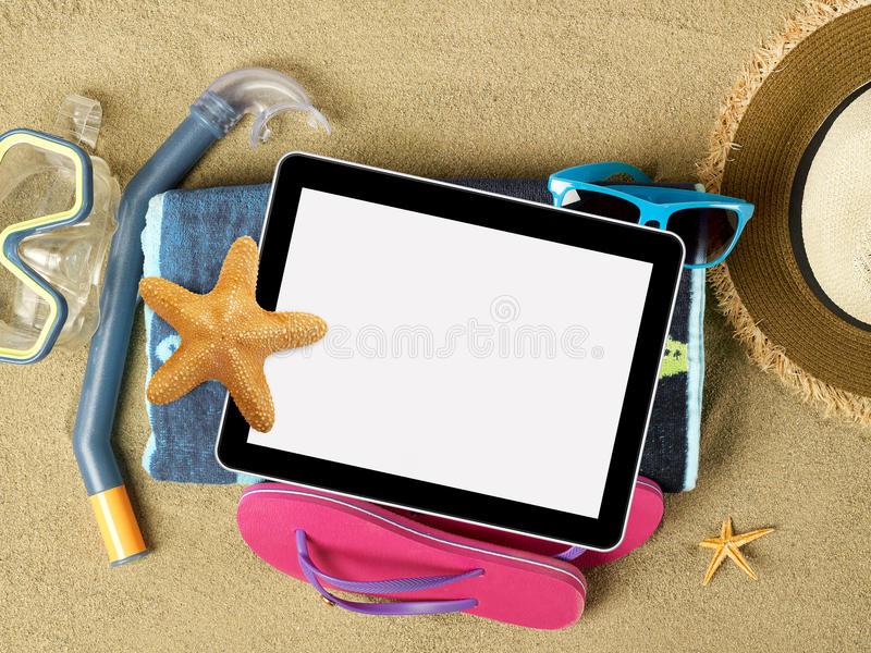Tablet and beach accesories on sand stock photos