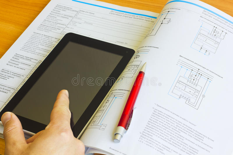 Tablet computer over engineering journal stock photo