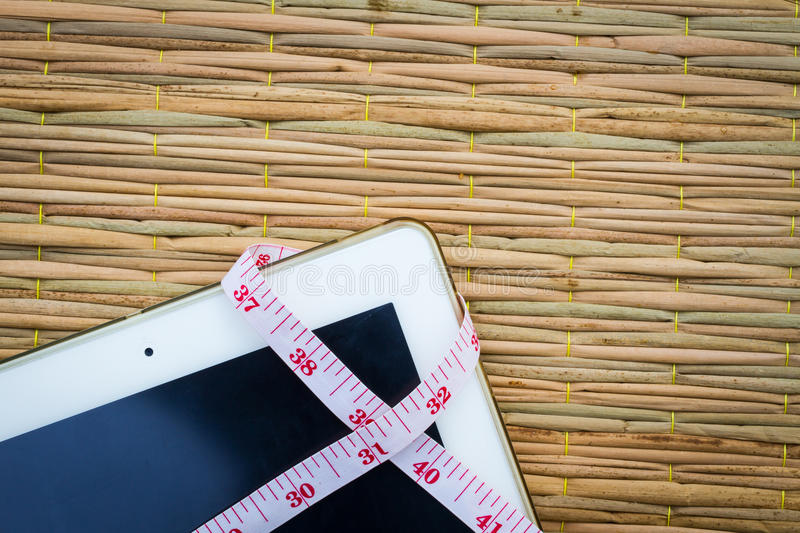 Tablet computer on traditional mat with measuring tape for weig. Ht loss and diets, copyspace royalty free stock photography