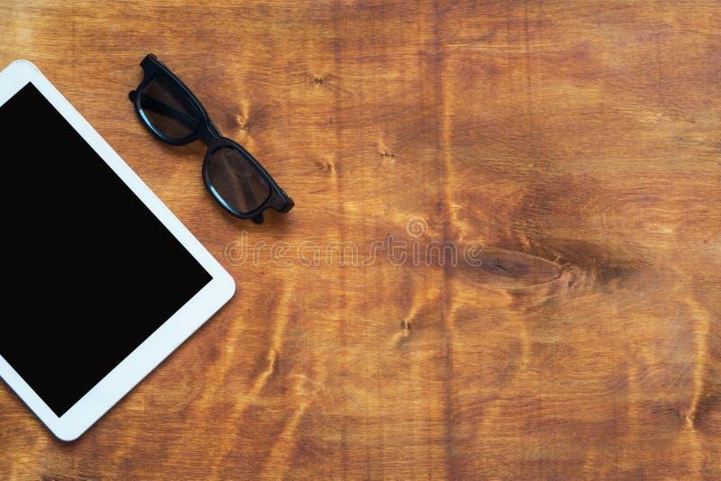 Tablet-Computer und schwarze Gläser auf hölzernem Hintergrund Kopieren Sie Platz stockfoto
