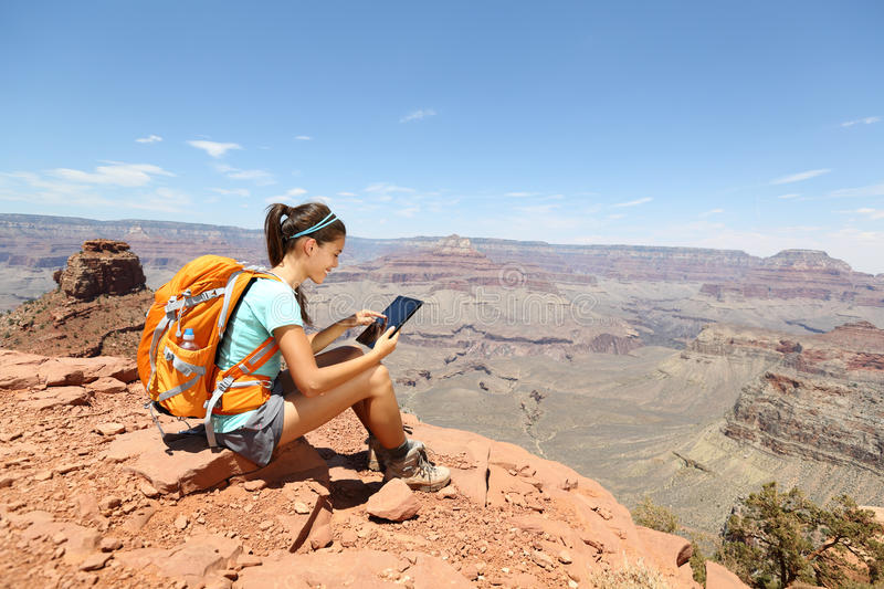 Tablet computer woman hiking in Grand Canyon. Using travel app or map during her hike. Multiethnic hiker girl relaxing on South Kaibab Trail, south rim of Grand