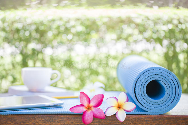 Tablet and a cup of coffee on a yoga mat. Outdoor scence royalty free stock images
