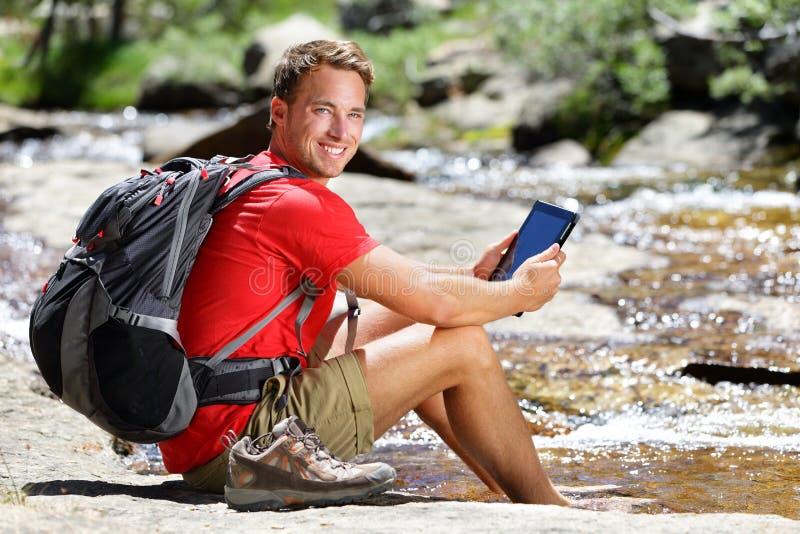 Tablet de lezing van de wandelingsmens ebook of kaart in aard stock foto's