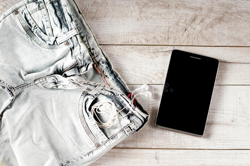 Tablet, earphones, jeans folded. On the wooden boards stock photos