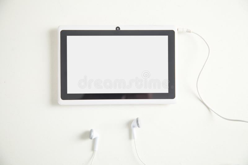 Tablet with a earphones on white desk stock images