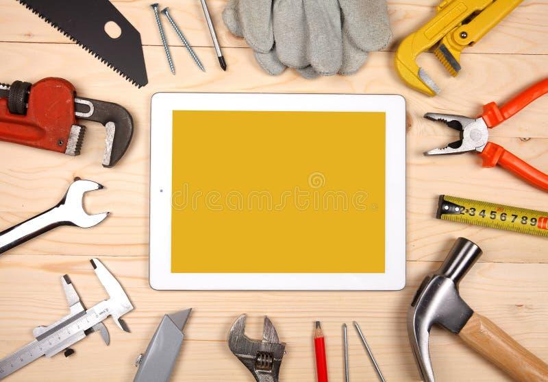 Tablet en reeks loodgieterswerk en hulpmiddelen op de houten lijst stock foto