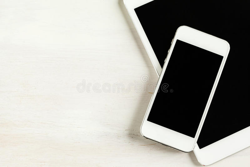 Tablet en telefoon dichte omhooggaand op houten achtergrond stock afbeeldingen