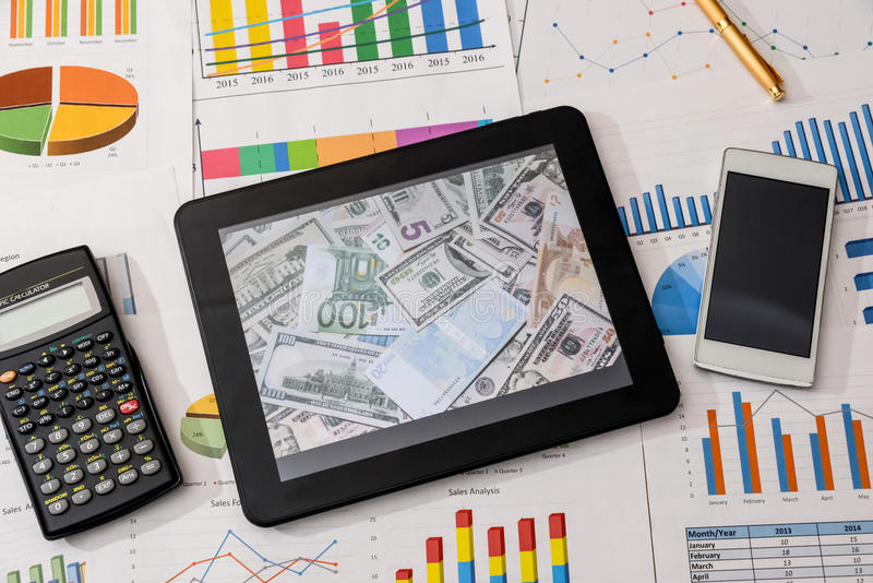 Tablet and financial charts, calculator, pen stock images