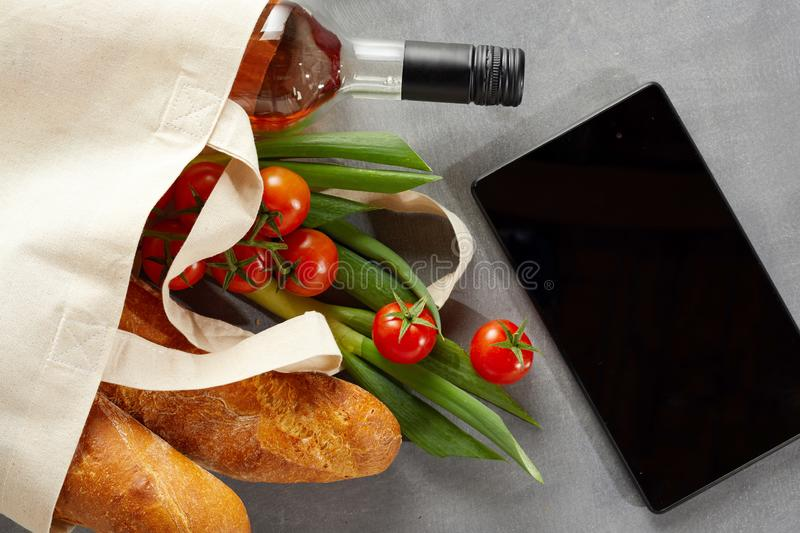 Tablet with fresh groceries in reusable bag stock image