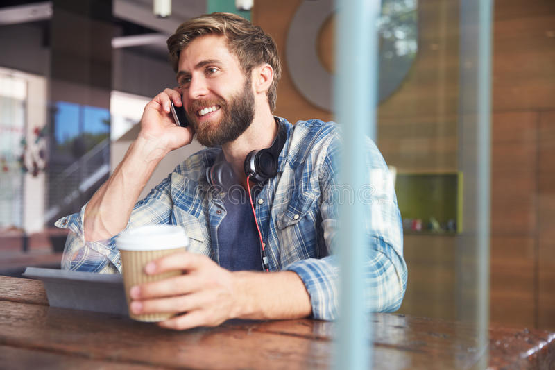 Tablet Geschäftsmann-On Phone Usings Digital in der Kaffeestube stockbild