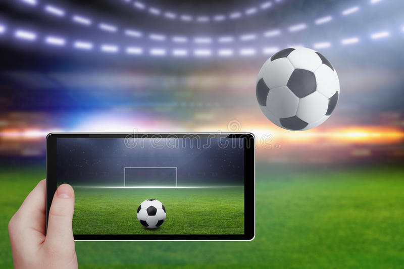 Tablet in hand, soccer stadium royalty free stock photography
