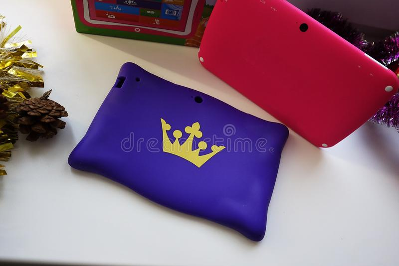 Tablet in the hands of a child. Tablet with a bright cover royalty free stock images